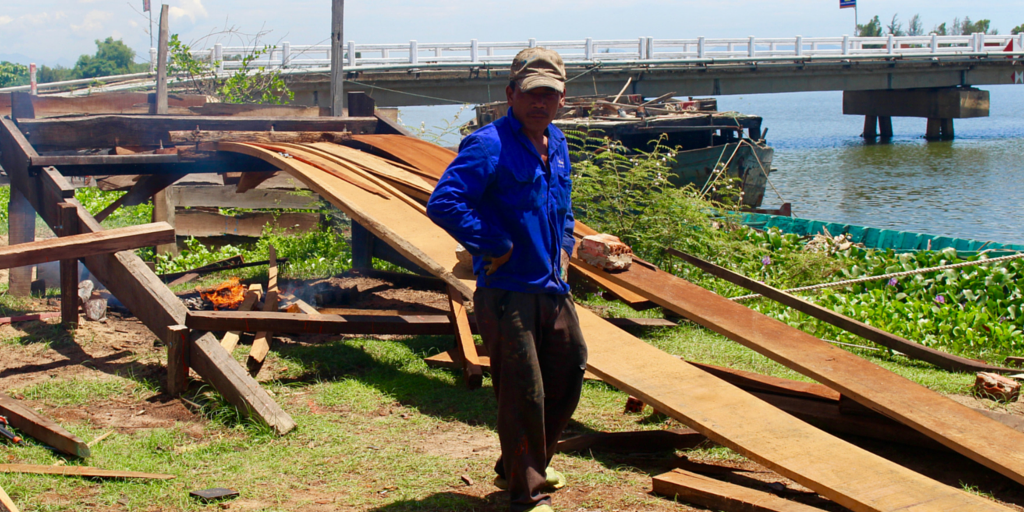 This man bends and burns the wood that will be used to construct the boat.